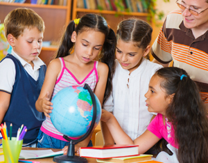 Portrait of pupils looking at globe with their teacher